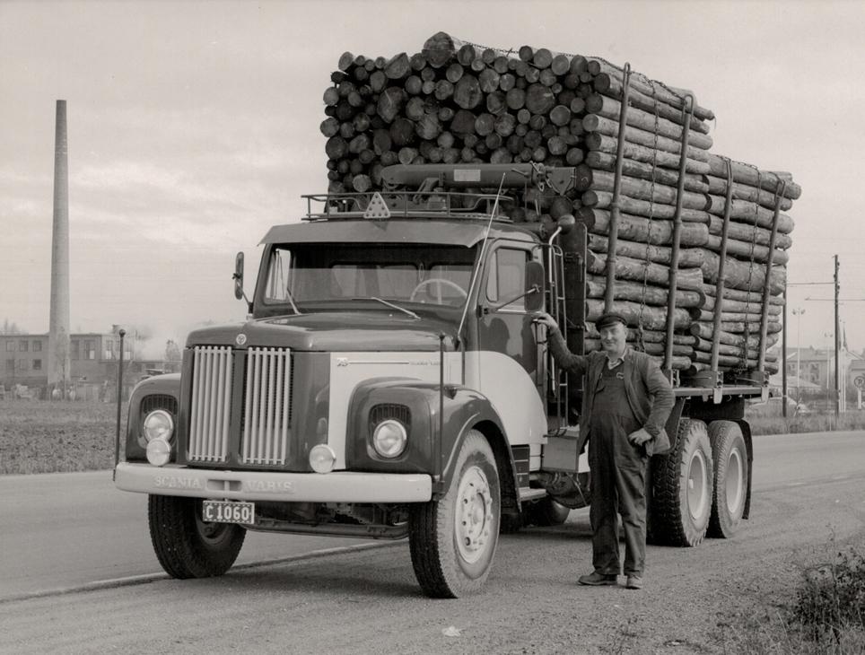 År 1961. Ett svart/vitt foto av grundaren Sven Jansson som står bredvid en blank ny Scania lastbil med flak. Flaket är lastat högt med timmer.